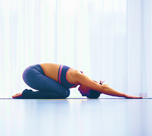Woman performing balasana yoga pose in a white studio