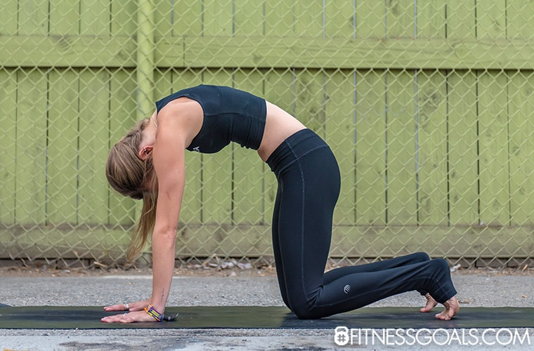 Marjariasana yoga pose modification with toes tucked to relieve tension in the top of the feet